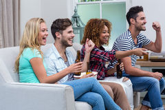 Rozochoceni etniczni przyjaciele cieszy się mecz piłkarskiego w domu Zdjęcia Stock