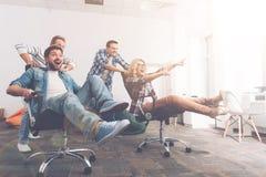 Rozochoceni koledzy ma zabawę w biurowych krzesłach Zdjęcia Stock
