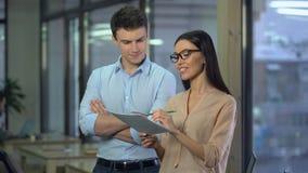 Rozochoceni kreatywnie projektanci dyskutuje rozkaz, mężczyzna chwali pracę azjatykcia kobieta zdjęcie wideo