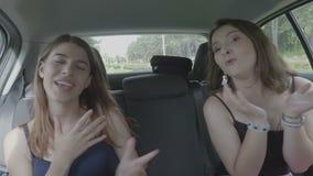 Rozochoceni młodzi żeńscy najlepszy przyjaciele śpiewa, tanczy w samochodzie na wycieczki samochodowej odświętności wolności i ma zdjęcie wideo