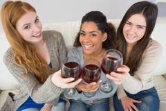 Rozochoceni młodzi żeńscy przyjaciele wznosi toast win szkła zdjęcia stock
