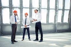 Rozochoceni młodzi budowniczowie dyskutują plan fotografia stock
