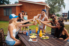 Rozochoceni młodzi ludzie świętuje piwo na plenerowym przyjęciu i pije Zdjęcia Royalty Free