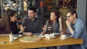 Rozochoceni młodzi przyjaciele są opowiadający udzielenie wiadomość i gestykulujący podczas gdy siedzący przy stołem w nowożytnej zdjęcie wideo