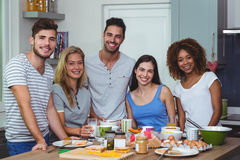 Rozochoceni młodzi przyjaciele stoi przy stołem zdjęcia stock
