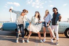 Rozochoceni młodzi przyjaciele tanczy wpólnie outdoors fotografia stock