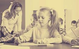 Rozochoceni małe dzieci z nauczyciela rysunkiem w sala lekcyjnej obrazy royalty free