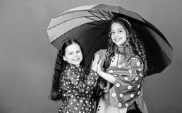 rozochoceni modnisi?w dzieci, zakon ?e?ski Rodzinne wi?zi Ma?e dziewczynki w deszczowu Jesieni moda Podeszczowa ochrona t?cza obrazy stock