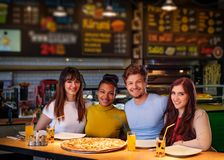 Rozochoceni multiracial przyjaciele ma zabawy łasowanie w pizzeria zdjęcie stock
