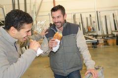 Rozochoceni pracownicy ma lunchu łasowania kanapkę w warsztacie Zdjęcia Royalty Free