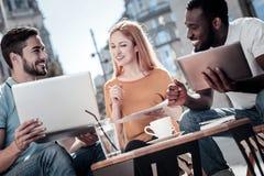 Rozochoceni przedsiębiorcy pracuje na projekcie podczas gdy siedzący w kawiarni Obraz Stock