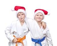 Rozochoceni przyjaciele ściska w kimonie i jest ubranym Santa kapelusz Fotografia Royalty Free