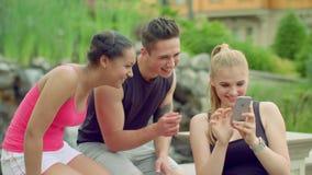 Rozochoceni przyjaciele ma zabawę w parku Młodzi ludzie używa telefon plenerowego przy latem zdjęcie wideo