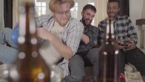 Rozochoceni przyjaciele ogląda telewizyjnego obsiadanie na leżance Na stole są puste piwne butelki Faceci błaź się zdjęcie wideo