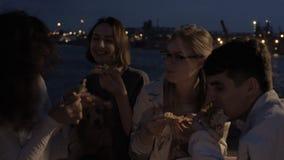 Rozochoceni przyjaciele przy partyjną łasowanie pizzą zbiory wideo