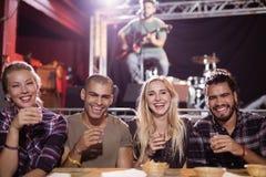 Rozochoceni przyjaciele siedzi stronę popierają kogoś z muzykiem w tle - obok - Zdjęcia Stock