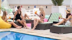 Rozochoceni przyjaciele w kostiumu kąpielowego napoju barwili napoje na słońca lounger przy tarasem zbiory
