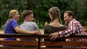 Rozochoceni rodzice i ich nastoletni dzieci planuje weekend na ławce w parku obrazy royalty free