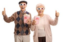 Rozochoceni seniory z 3D szkłami i popkornem robi kciukowi up Zdjęcia Royalty Free