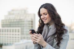 Rozochocona ładna brunetka w zimy odzieżowym dosłaniu tekst na ona Zdjęcia Stock
