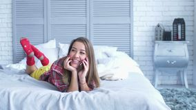 Rozochocona ładna kobieta opowiada na telefonie komórkowym na łóżku zdjęcie wideo