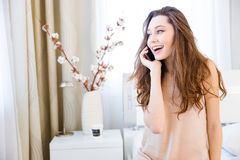 Rozochocona ładna młoda kobieta opowiada na telefonie komórkowym w domu Zdjęcia Royalty Free
