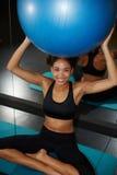 Rozochocona afro kobieta śmia się podczas gdy chwyt balansowa piłka w centrum zdrowia Fotografia Stock