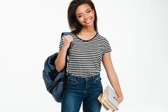 Rozochocona afrykańska studencka dziewczyna jest ubranym plecaka i trzyma książki Zdjęcie Stock
