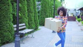 Rozochocona amerykanin afrykańskiego pochodzenia kobieta z afro fryzurą z pudełkiem zbiory