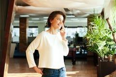 Rozochocona atrakcyjna młoda kobieta opowiada na telefonie komórkowym w biurze zdjęcia royalty free