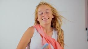 Rozochocona atrakcyjna nastoletnia dziewczyna śpiewa pieśniową mienie gręplę jak mikrofon zdjęcie wideo