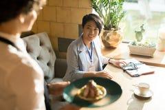 Rozochocona Azjatycka kobieta ono uśmiecha się przy kelnerką z jej naczyniem fotografia royalty free