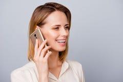 Rozochocona blond dziewczyna z promieniejącym uśmiechem opowiada na jej telefonie obrazy stock