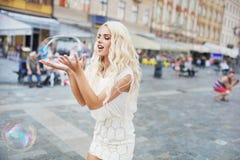 Rozochocona blondynka niesie ogromnego mydlanego bąbel obraz stock