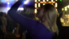 Rozochocona blondynki dziewczyna aktywnie tanczy przy koncertem, cieszy się muzykę, positivity zdjęcie wideo