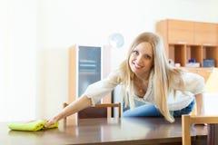 Rozochocona blondynki kobieta wyciera pył od stołu Obraz Stock