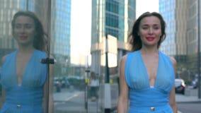 Rozochocona brunetki dziewczyna w błękit sukni odprowadzeniu w kierunku kamery na ulicznym, super zwolnione tempo strzale, 250 fp zbiory