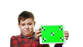 Rozochocona chłopiec trzyma pastylkę w jego ręce z zielonym ekranem zbiory