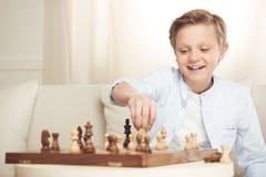 Rozochocona chłopiec bawić się szachowy samotnego w domu obraz stock