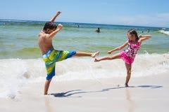 Rozochocona chłopiec i dziewczyna bawić się na plaży obraz royalty free