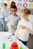 Rozochocona chłopiec ogląda jego kolega z klasy zachowania chemicznego eksperyment obrazy royalty free