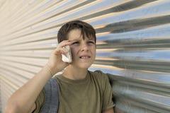 Rozochocona chłopiec używa telefon komórkowego obrazy stock
