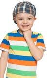 Rozochocona chłopiec w nakrętek spojrzeniach naprzód zdjęcie stock