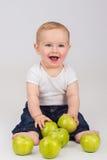 Rozochocona chłopiec z zielonym jabłkiem jest uśmiechnięta Fotografia Stock
