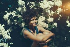 Rozochocona czarna dziewczyna przed ścianą biali kwiaty Zdjęcia Royalty Free