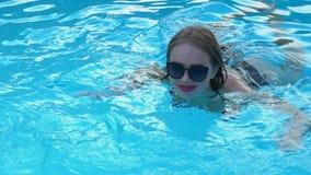 Rozochocona dama pływa w jasnej błękitne wody w moda okularach przeciwsłonecznych, lato relaksuje zbiory