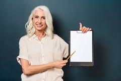 Rozochocona dojrzała stara kobieta pokazuje pustego schowek Obraz Stock