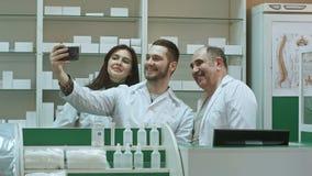 Rozochocona drużyna farmaceuta i stażyści bierzemy selfie przez smartphone przy miejscem pracy Fotografia Stock