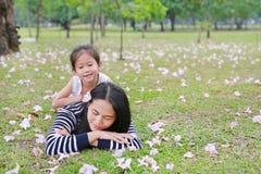 Rozochocona dziecko dziewczyna cuddle jej mamy lying on the beach na zieleni polu z spadek menchii kwiatem w ogr?dzie plenerowym  obrazy royalty free