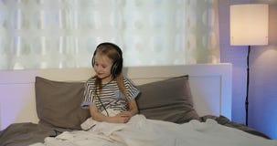 Rozochocona dziewczyna kłama w łóżku i słuchaniu muzyka w hełmofonach zbiory